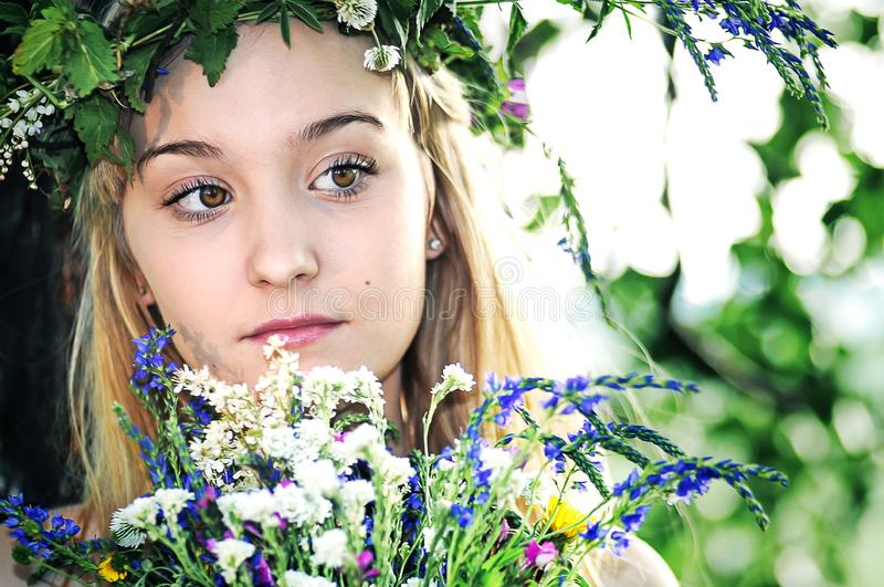 Portrait of a blonde girl with a wreath of flowers in the summer near the tree stock photography