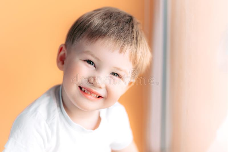 Portrait of blonde happy joyful beautiful cute little boy looking at camera on orange background stock photo