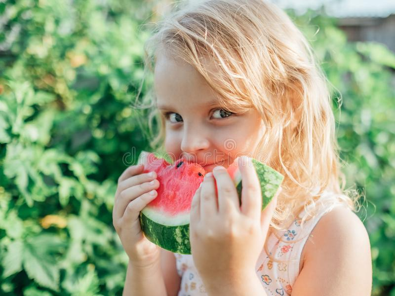 Portrait of blonde little girl with watermelon royalty free stock images