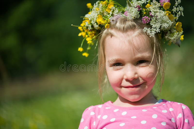 Blonde little girl with a wreath of flowers on her head stock photography