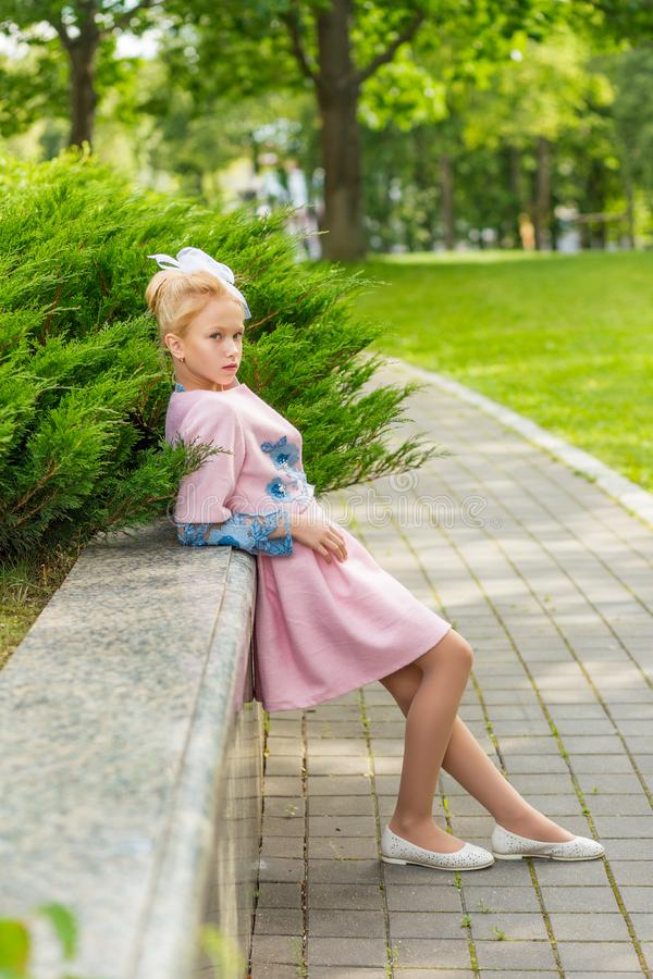 Portrait of a blonde in pink attire in a park outdoors. stock image
