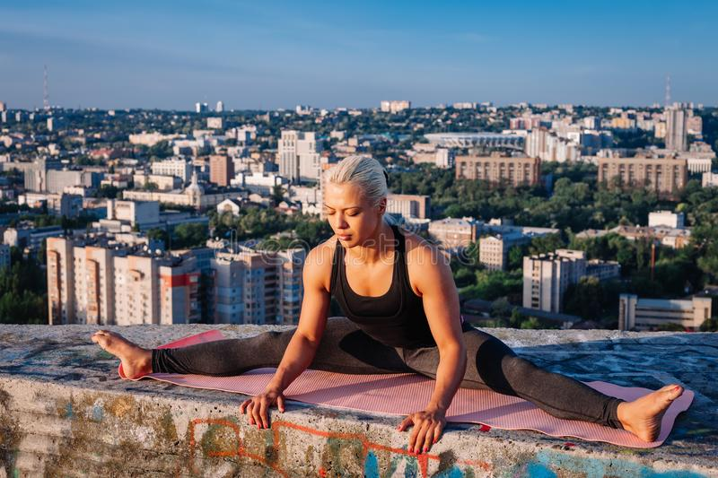 Portrait of blonde strong woman in sportwear doing workout stretching on the roof of skyscraper above the big city at early royalty free stock photography