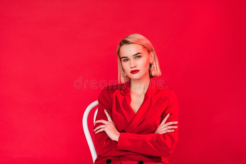 portrait of blonde stylish girl posing in red jacket with crossed arms, stock photos