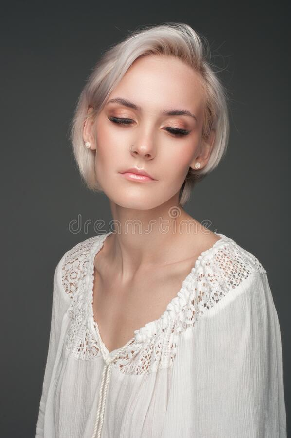 Portrait of a blonde in a white blouse on a dark gray background royalty free stock photo