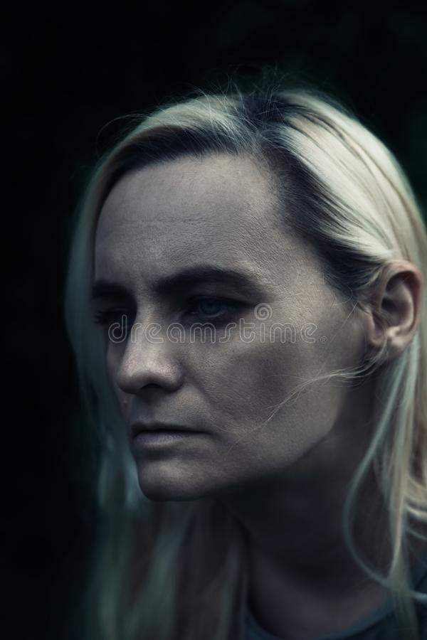 Portrait of blonde woman in a dark, creepy feel, with dark shadows hiding her eyes. Negative emotions, horror royalty free stock images