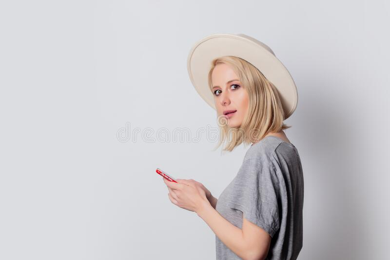 Beautiful blonde woman using mobile phone on white background royalty free stock images