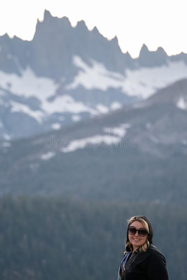 Portrait of a blonde woman wearing a hoodie and sunglasses at Minaret Vista point in Mammoth Lakes, showing scale of the large royalty free stock photography