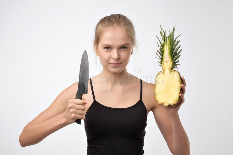 Portrait of blonde woman who keeps pineapple and knife in hands against white background stock photography