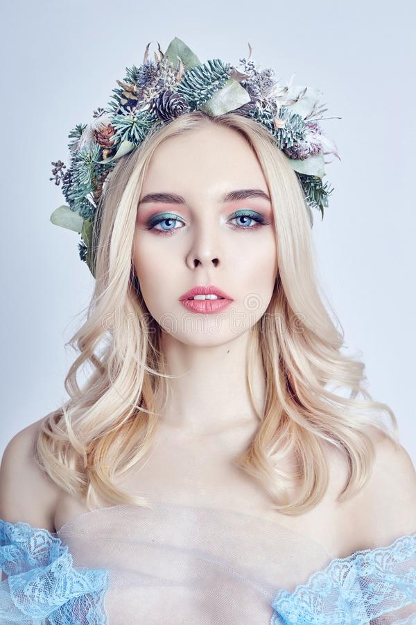 Portrait of a blonde woman with a wreath on her head and a blue delicate light transparent dress. Big blue eyes and beautiful skin. Fabulous mysterious magical royalty free stock image