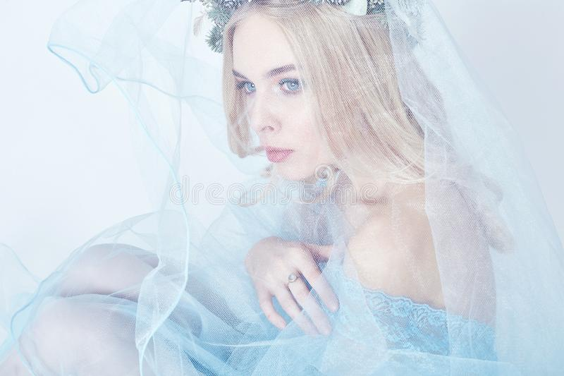 Portrait of a blonde woman with a wreath on her head and a blue delicate light transparent dress. Big blue eyes and beautiful skin. Fabulous mysterious magical royalty free stock photos