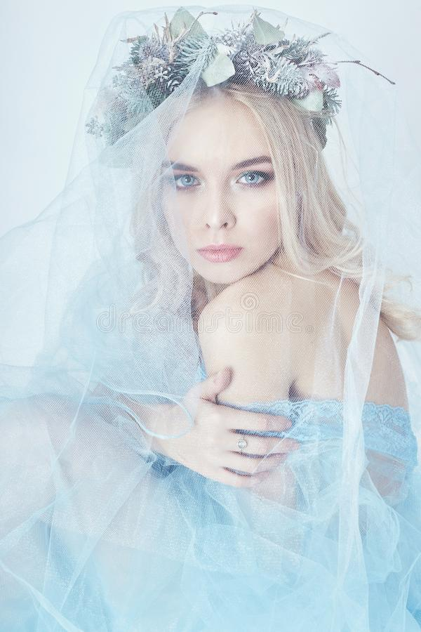 Portrait of a blonde woman with a wreath on her head and a blue. Delicate light transparent dress. Big blue eyes and beautiful skin. Fabulous mysterious magical stock photos