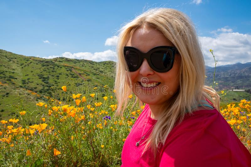Portrait of a blonde young adult woman in a field of poppies and mixed wildflowers during the California super bloom royalty free stock image