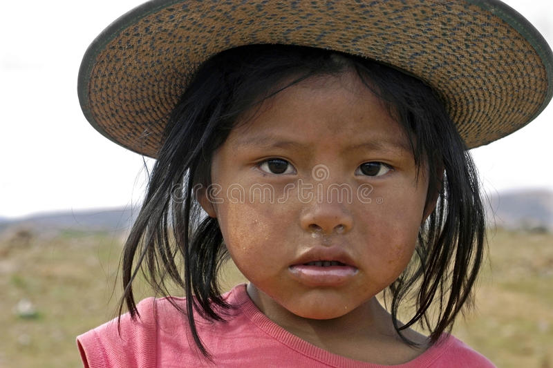 Portrait Bolivian girl with shy facial expression. Bolivia, city Cochabamba: closeup of young Indian girl with modern bolder hat and runny nose in a suburb of royalty free stock photos