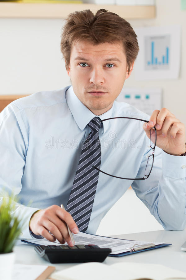 Portrait of bookkeeper or financial inspector holding his glasses stock photography