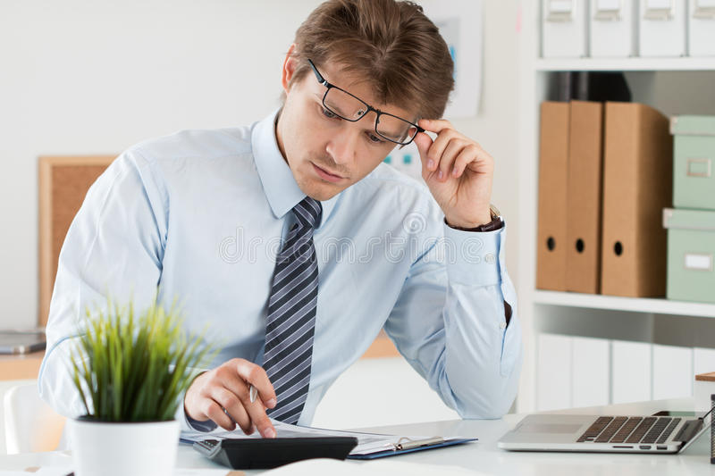 Portrait of bookkeeper or financial inspector making calculation royalty free stock photography