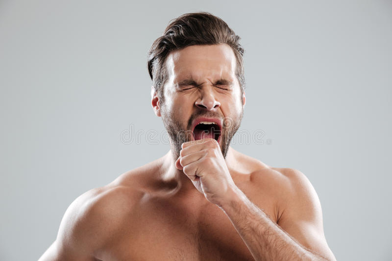 Portrait of a bored beraded man with naked shoulders yawning royalty free stock photos