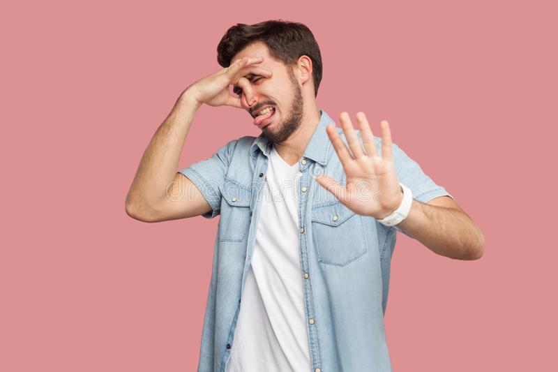 Portrait of bored or confused handsome bearded young man in blue casual style shirt standing, pinching his nose and showing stop. Gesture hand sign. indoor royalty free stock images