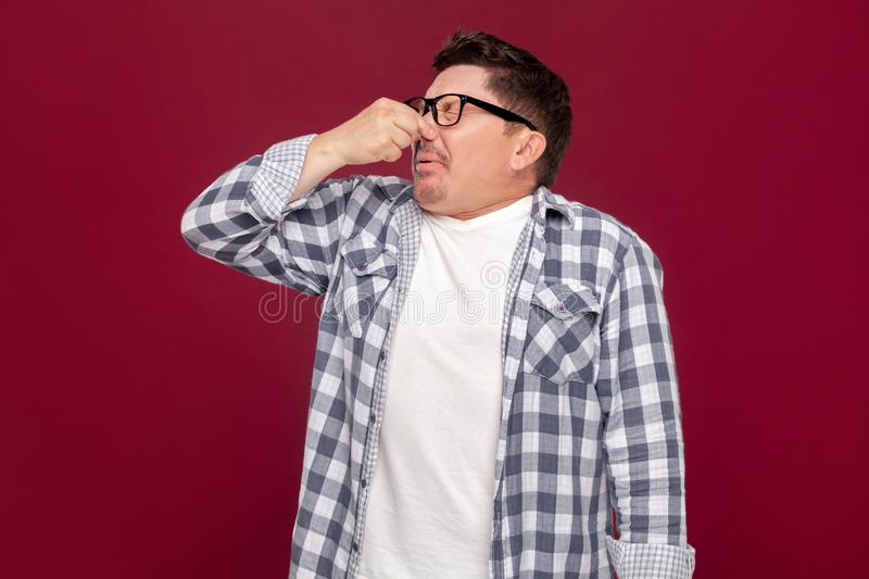 Portrait of bored handsome middle aged business man in casual checkered shirt and eyeglasses standing and blocking his nose. Because bad smell. indoor studio royalty free stock photos