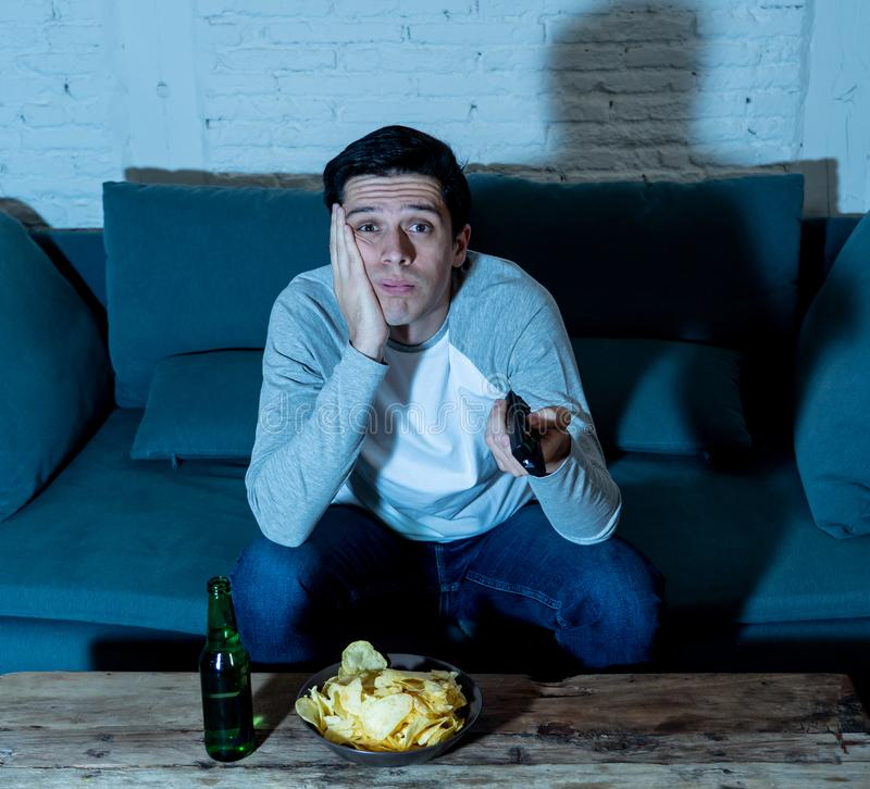Portrait of bored sleepless young man sitting on the couch watching TV and drinking beer at night stock photos