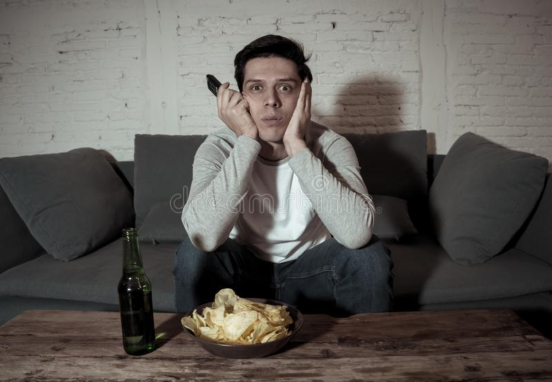 Portrait of bored sleepless young man sitting on the couch watching TV and drinking beer at night royalty free stock photos