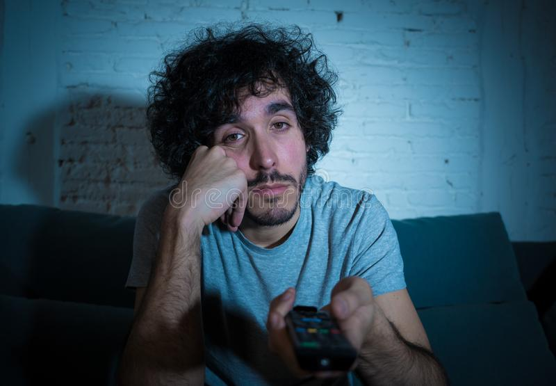 Portrait of bored sleepless young man sitting on the couch watching TV at night royalty free stock photo