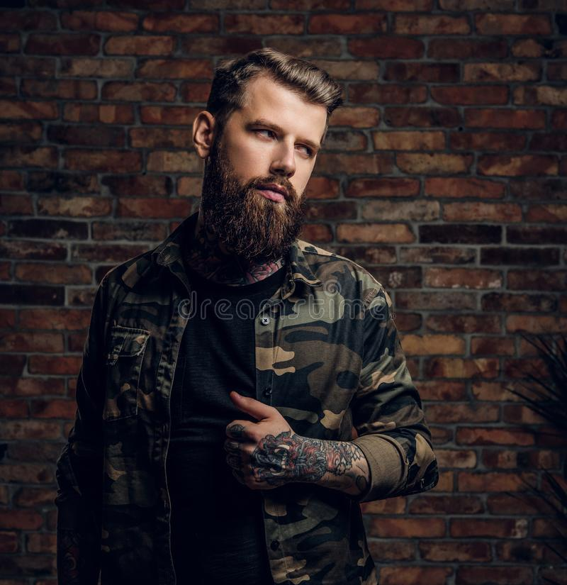 Portrait of a bored tattooed bearded guy in the military shirt. Studio photo against brick wall stock photography