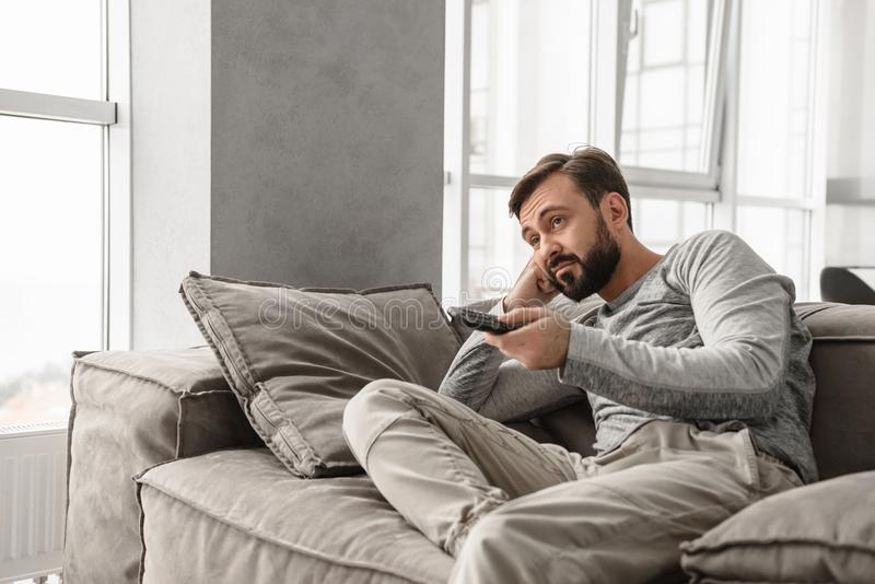 Portrait of a bored young man holding TV remote control stock image