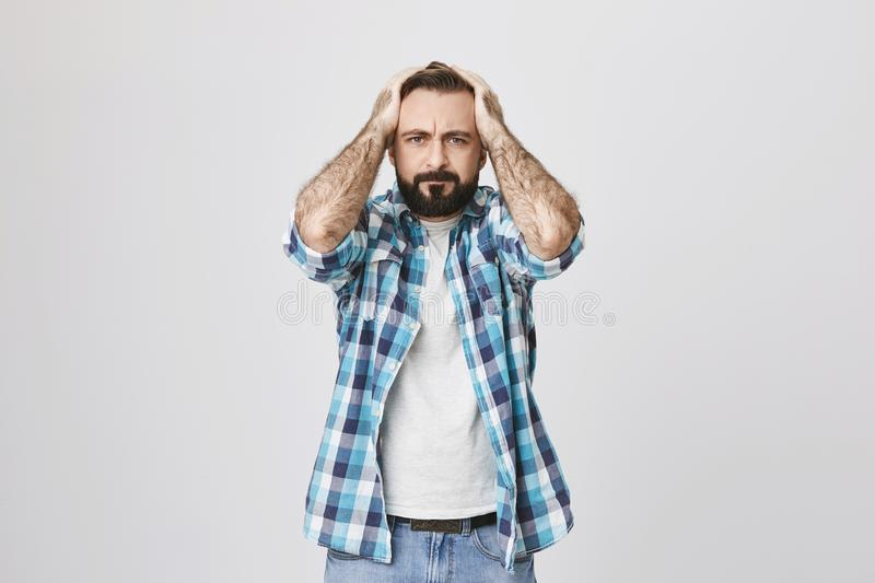 Portrait of bothered and devastated male adult, holding hands on hair, expressing that he do not know what to do, over royalty free stock images