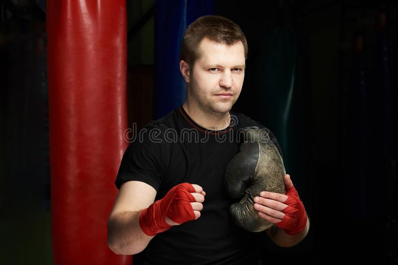 Portrait of boxing man. Portrait of boxing caucasian man with grungy gloves on gym background royalty free stock images