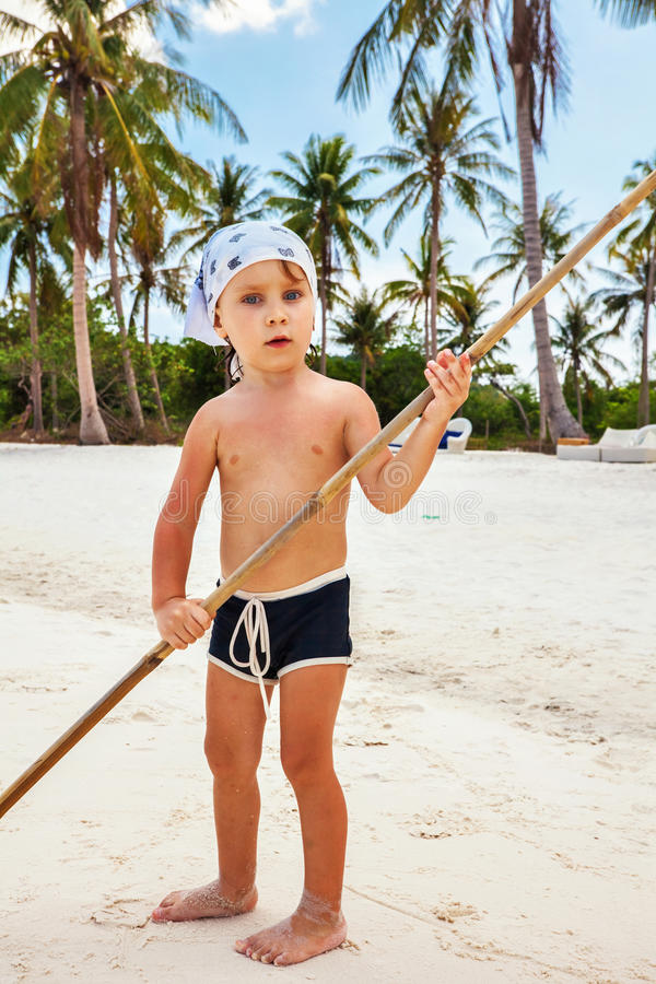 Portrait of a boy with a bamboo stick. On the beach royalty free stock photos
