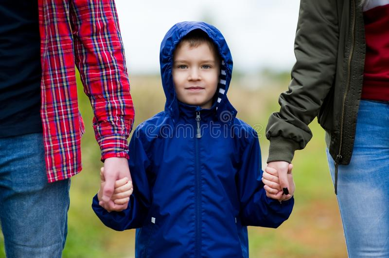 Portrait of a boy in a blue jacket who holds the hands of his parents. Close up royalty free stock photo
