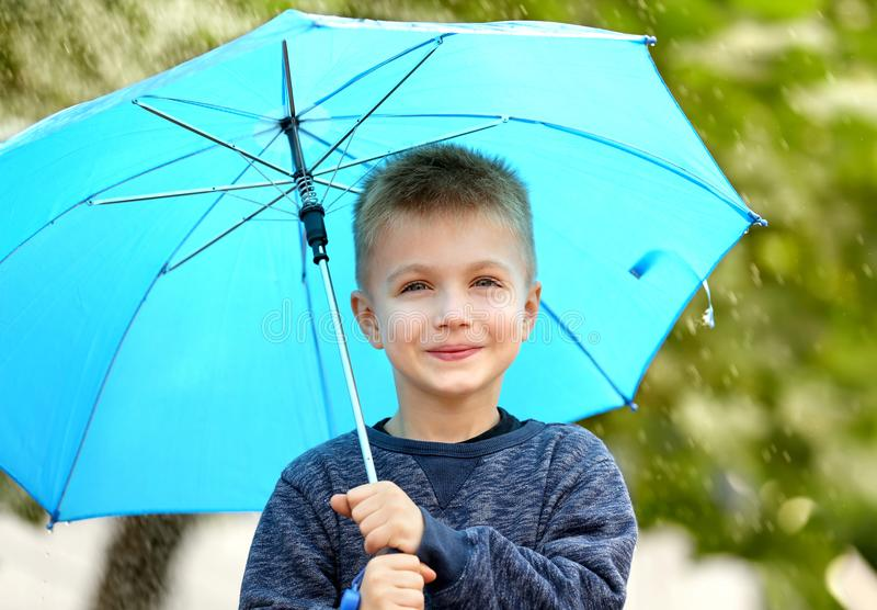 Portrait of boy with blue umbrella in rain royalty free stock image