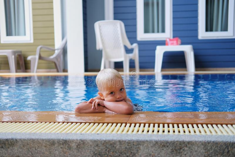 Portrait boy child in swimming pool home summer holiday, outdoors. Portrait of cute little boy with pigment spots on his face in swimming pool home summer royalty free stock images