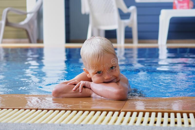 Portrait boy child in swimming pool home summer holiday, outdoors. Portrait of cute little boy with pigment spots on his face in swimming pool home summer royalty free stock image