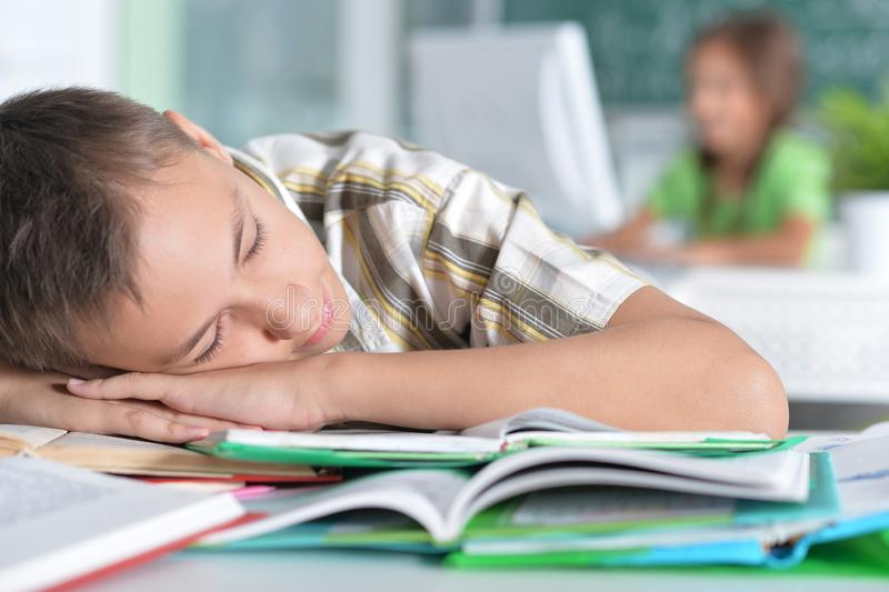Portrait of boy drawing sleeping on books stock image