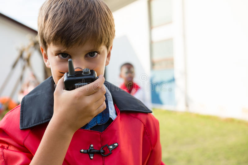 Portrait of boy with face paint using walkie talkie. During birthday party royalty free stock image