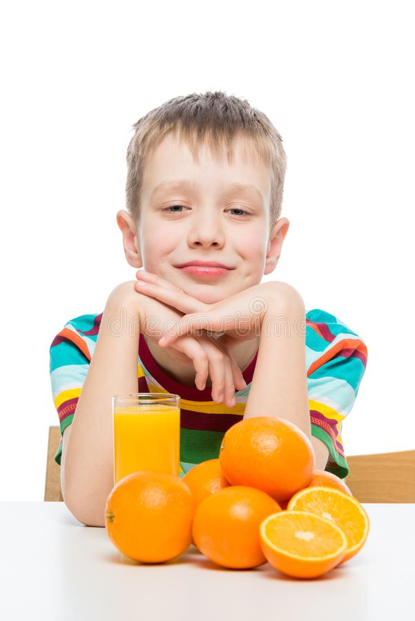 Portrait of a boy with fresh orange juice on a white background royalty free stock photography