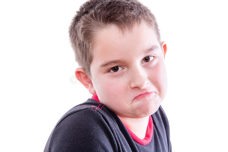 Portrait of Boy Frowning in White Studio. Head and Shoulders Close Up Portrait of Young Boy with Brown Eyes Looking at Camera with Down Turned Mouth in Studio stock photography