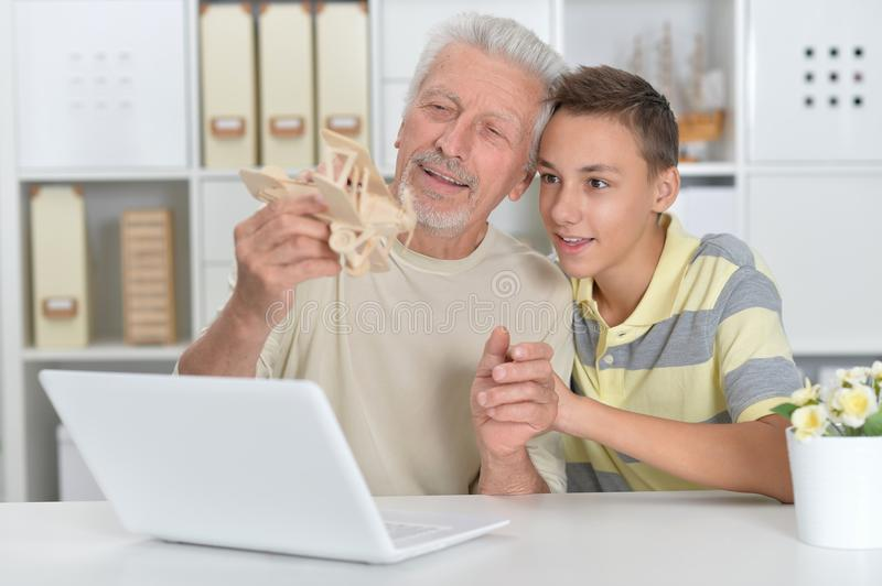 Boy and grandfather with a laptop and model of plane royalty free stock image