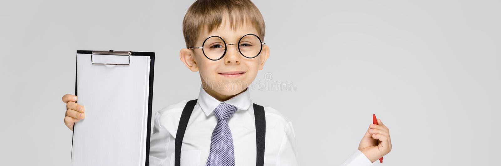 A charming boy in a white shirt, suspenders, a tie and light jeans stands on a gray background. The boy holds a pen and. Portrait of a boy on a gray background royalty free stock image