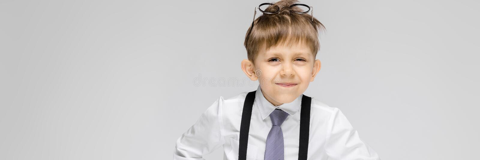 A charming boy in a white shirt, suspenders, a tie and light jeans stands on a gray background. Glasses on the head. Portrait of a boy on a gray background royalty free stock photography