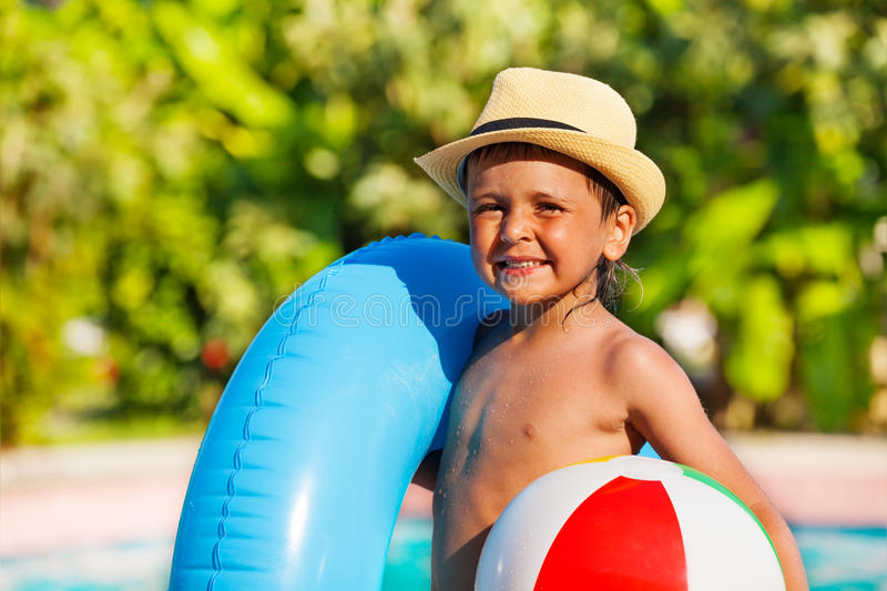 Portrait of boy in hat holding inflatable ring. Portrait of small boy in hat holding inflatable ring and ball standing near the swimming pool outside in summer royalty free stock photography