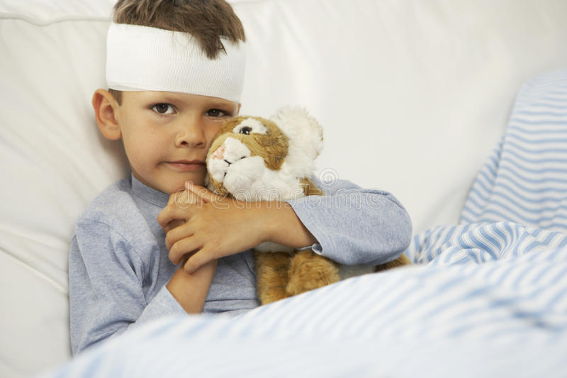Portrait of a boy hugging a stuffed toy with a bandage on his forehead stock image