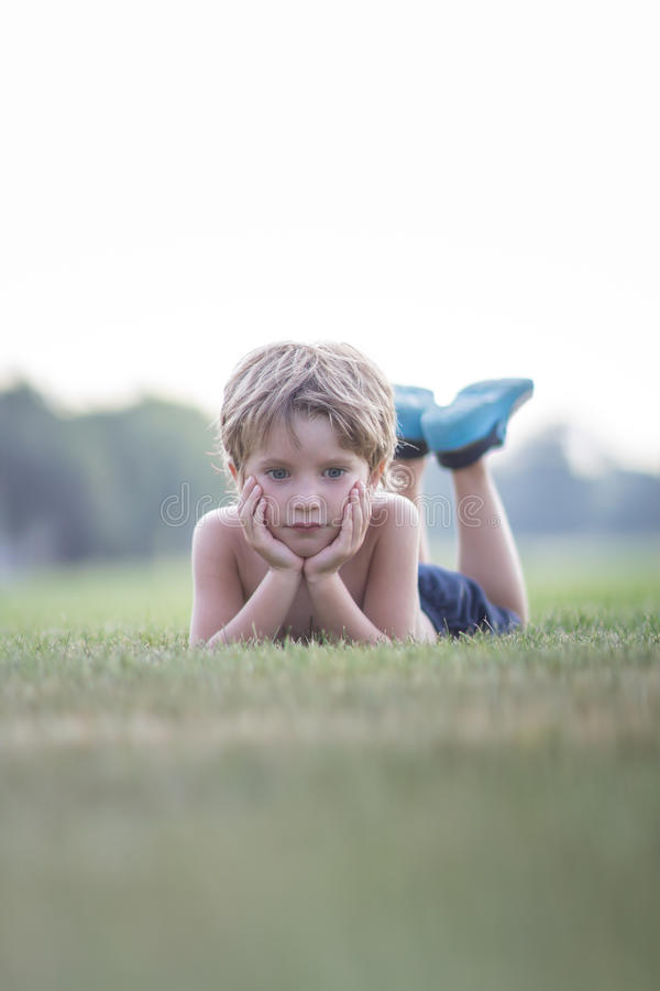 Portrait of a boy. Laying on grass royalty free stock photography