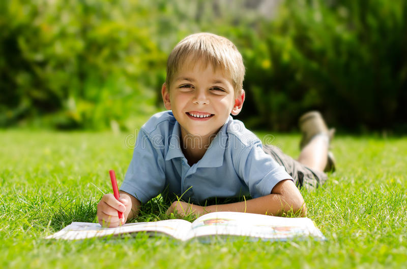 Portrait of a boy lying on the grass with a book