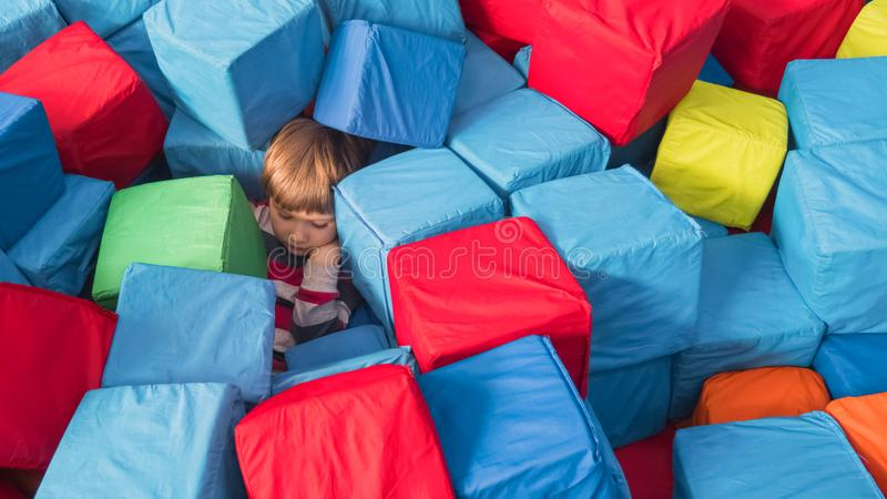 Portrait of boy playing with soft cubes. Boy sleeping at Entertainment Center. Kid among plastic cubes in children`s. Child in the playroom. Rest in children`s stock photos