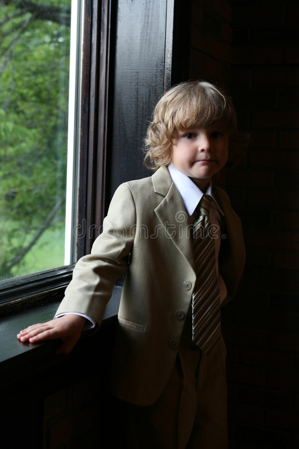 Portrait of boy in suit at the window royalty free stock image