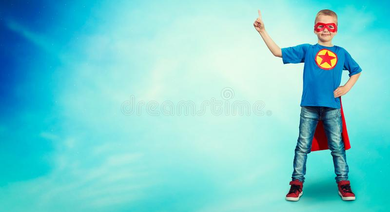Portrait of a boy in a superhero costume on a blue background. stock photo