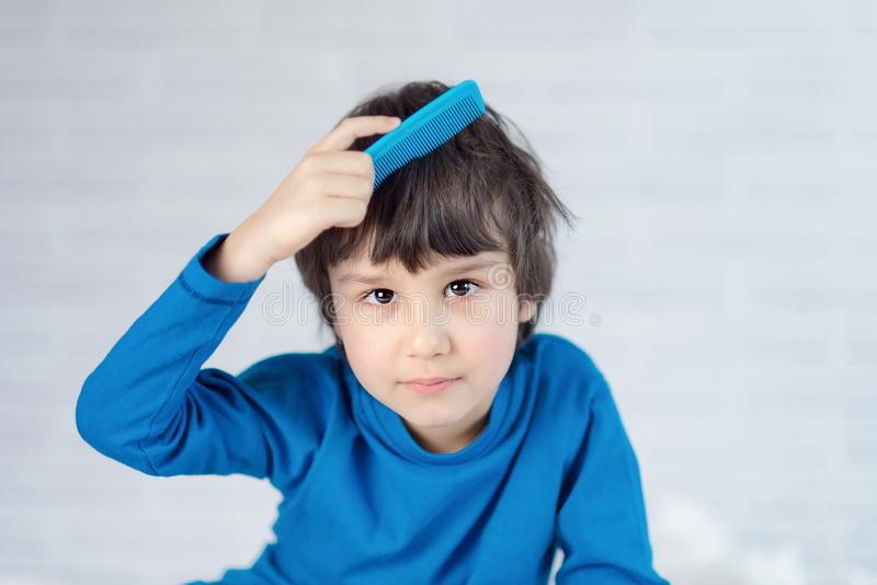 Portrait of a boy 5 years old combing his hair. Happy kid boy brushing his hair in the morning royalty free stock photography