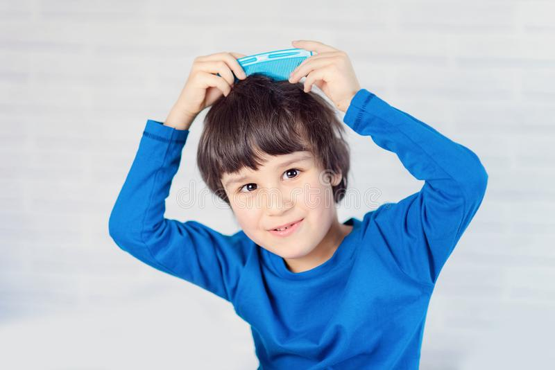 Portrait of a boy 5 years old combing his hair. Happy kid boy brushing his hair in the morning stock images